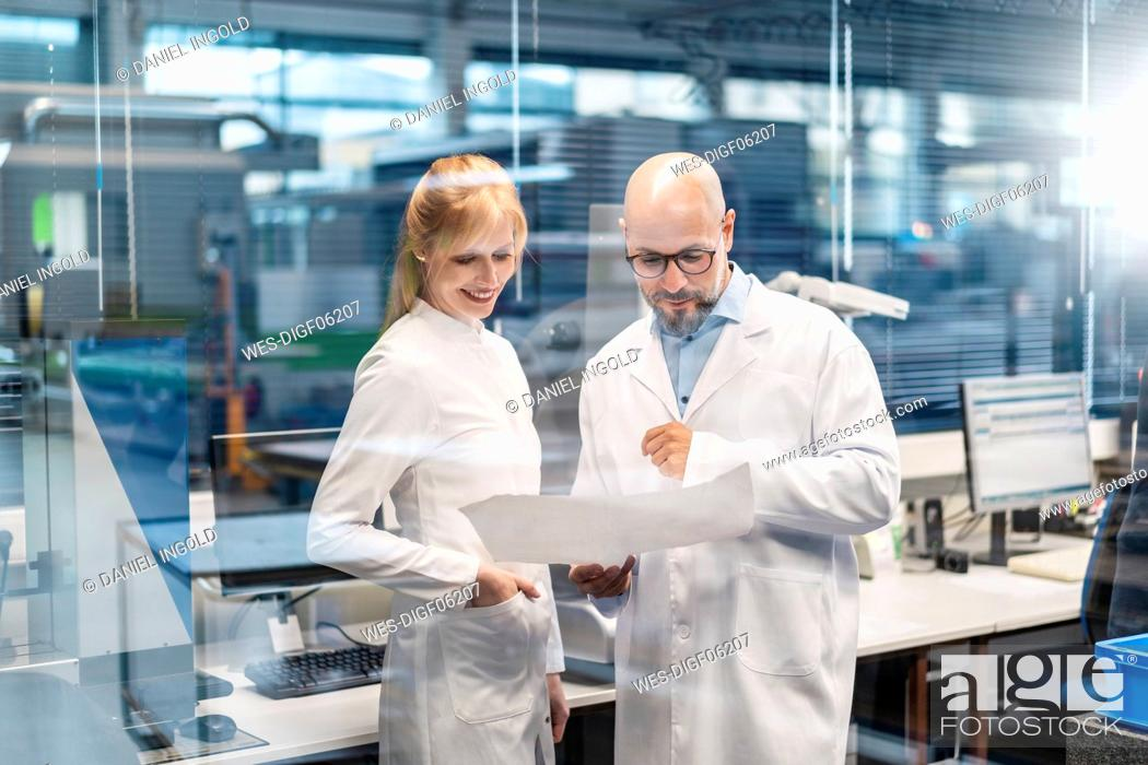 Stock Photo: Two technicians wearing lab coats looking at plan.