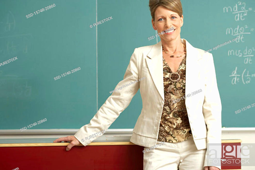 Stock Photo: Portrait of a professor standing in front of a blackboard and smiling.