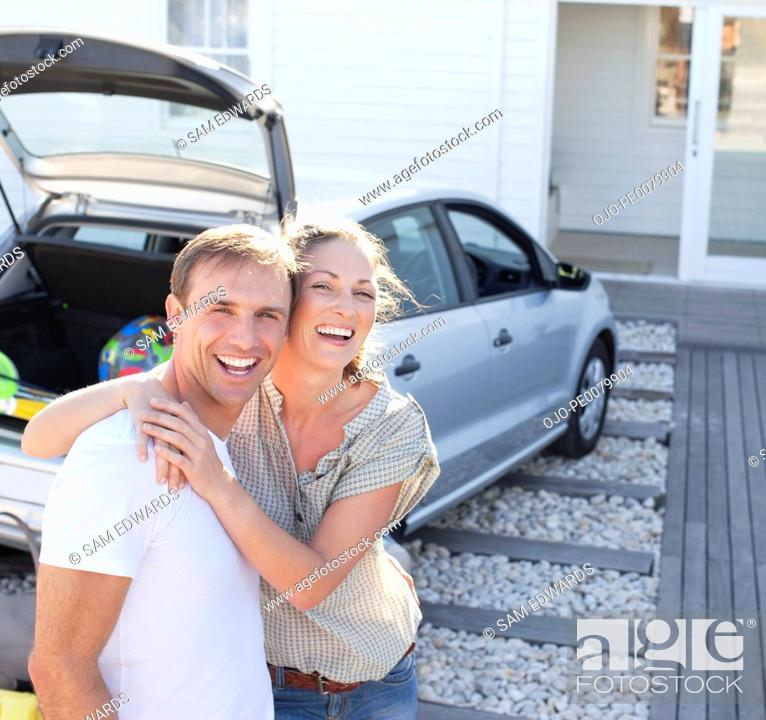 Stock Photo: Portrait of smiling couple hugging in driveway.