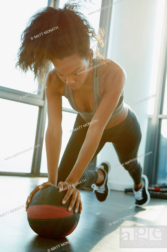 Stock Photo: Young woman working out in gym, using gym equipment.