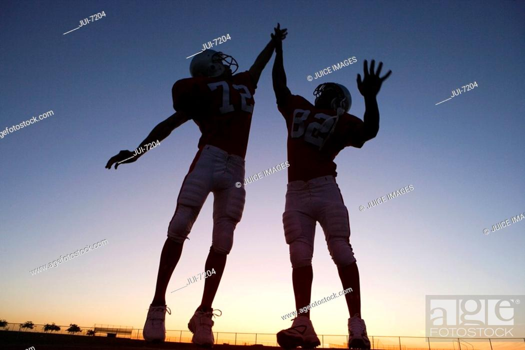 Stock Photo: Two American football players celebrating on pitch at sunset, jumping up, doing high-fives backlit.