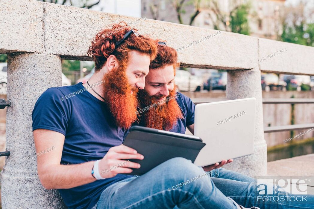 Stock Photo: Young male hipster twins with red hair and beards sitting on bridge browsing digital tablet.
