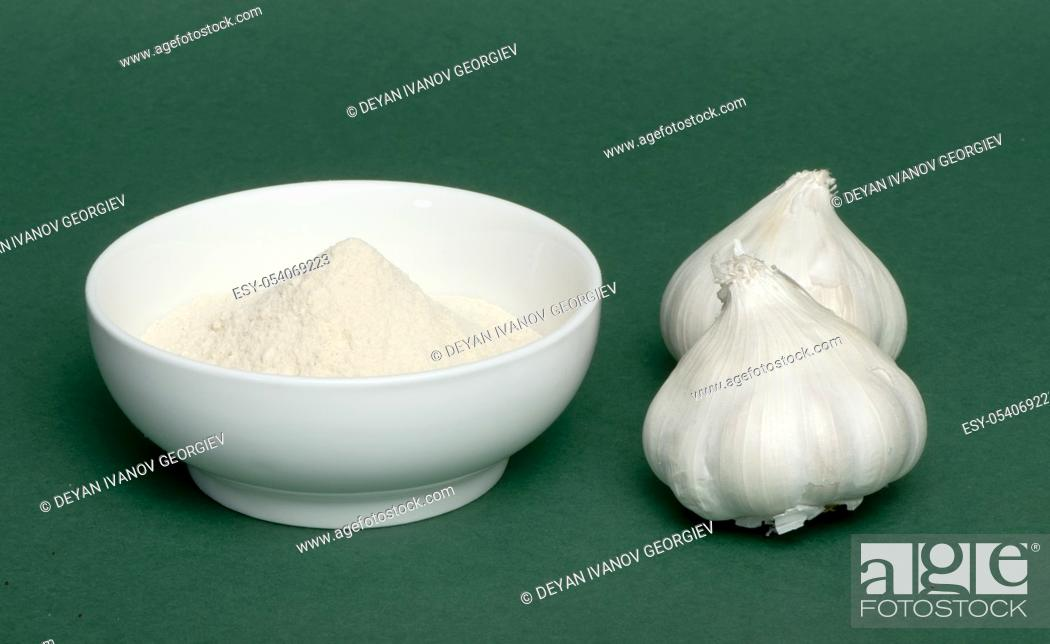 Stock Photo: Crushed garlic powder and whole heads of garlic. Green background.