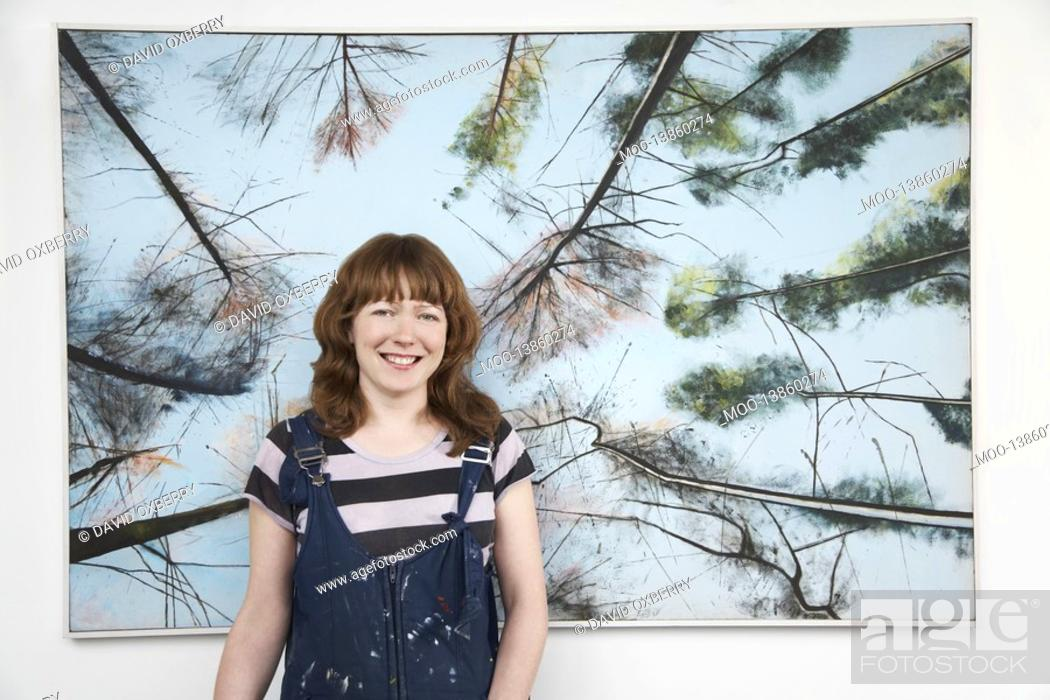 Stock Photo: Mid adult woman standing in front of large painting.