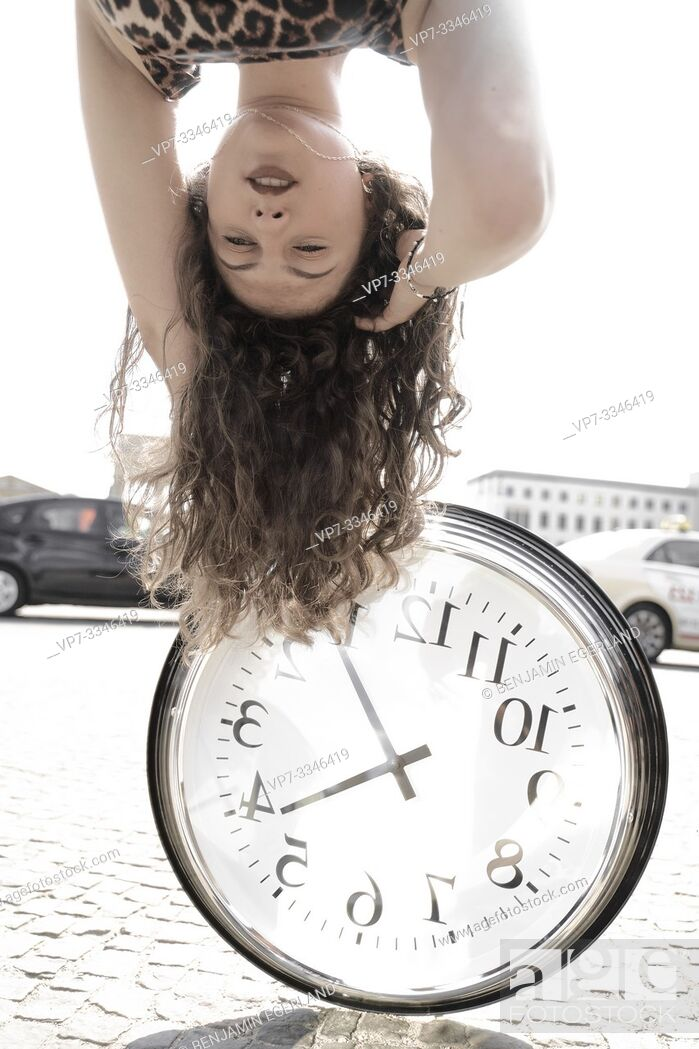Photo de stock: young emotional woman upside down with clock at street in city Berlin, Germany.