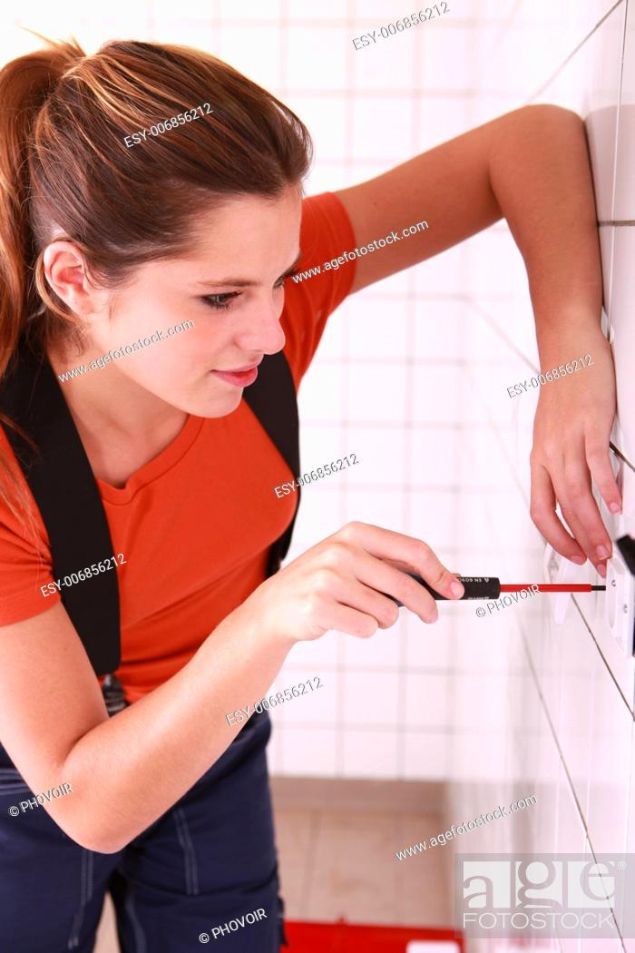 Stock Photo: Female electrician installing a wall socket.