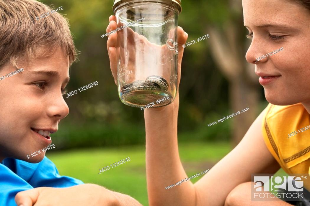 Stock Photo: Boys Looking at Snake in Jar.