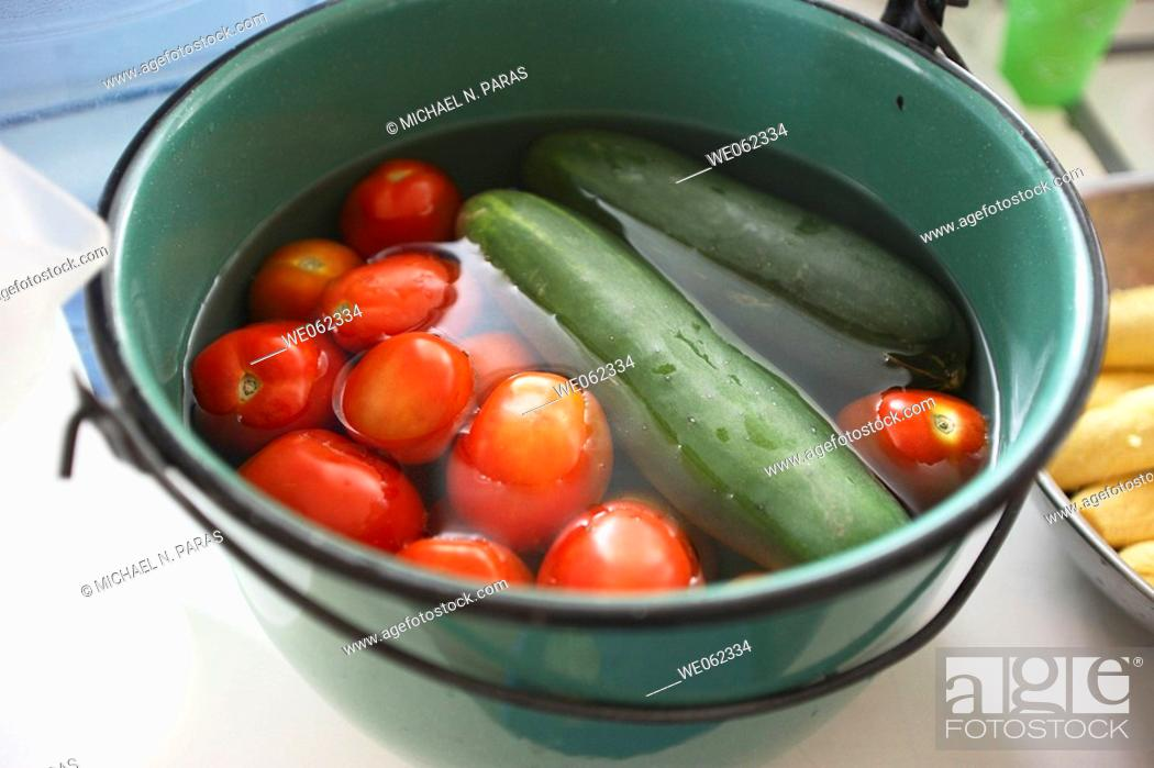 Stock Photo: Tomato and cucumber in pot of water.