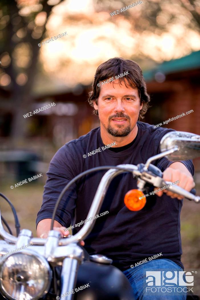 Stock Photo: USA, Texas, Mature man sitting on motorcycle, smiling.