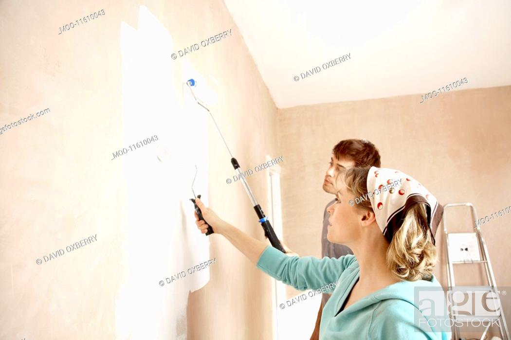 Stock Photo: Couple painting wall with paint rollers indoors.