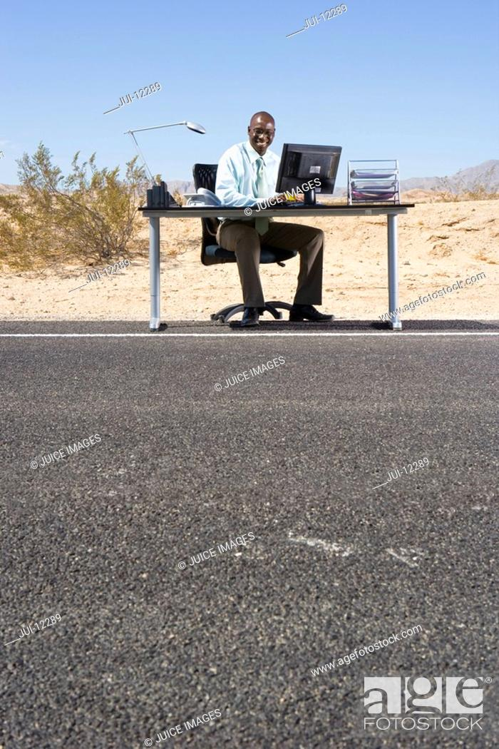 Stock Photo: Businessman at desk on side of road in desert, smiling, portrait, low angle view.