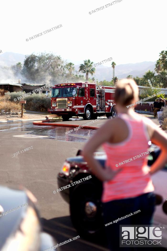 Stock Photo: A woman looking at the scene of a burning house in a suburb.