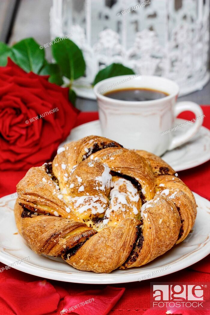 Stock Photo: Festive braided bread on white plate. Rose petals around, bouquet of roses in the background.