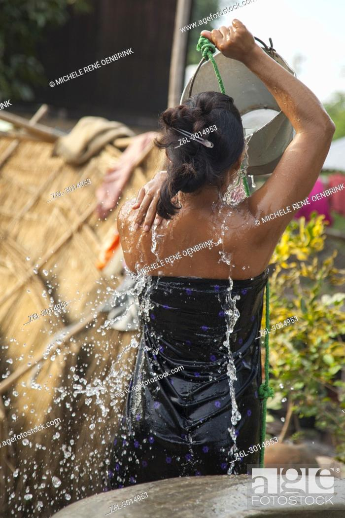 Stock Photo: Woman bathing in small town well outside Bagan Myanmar.