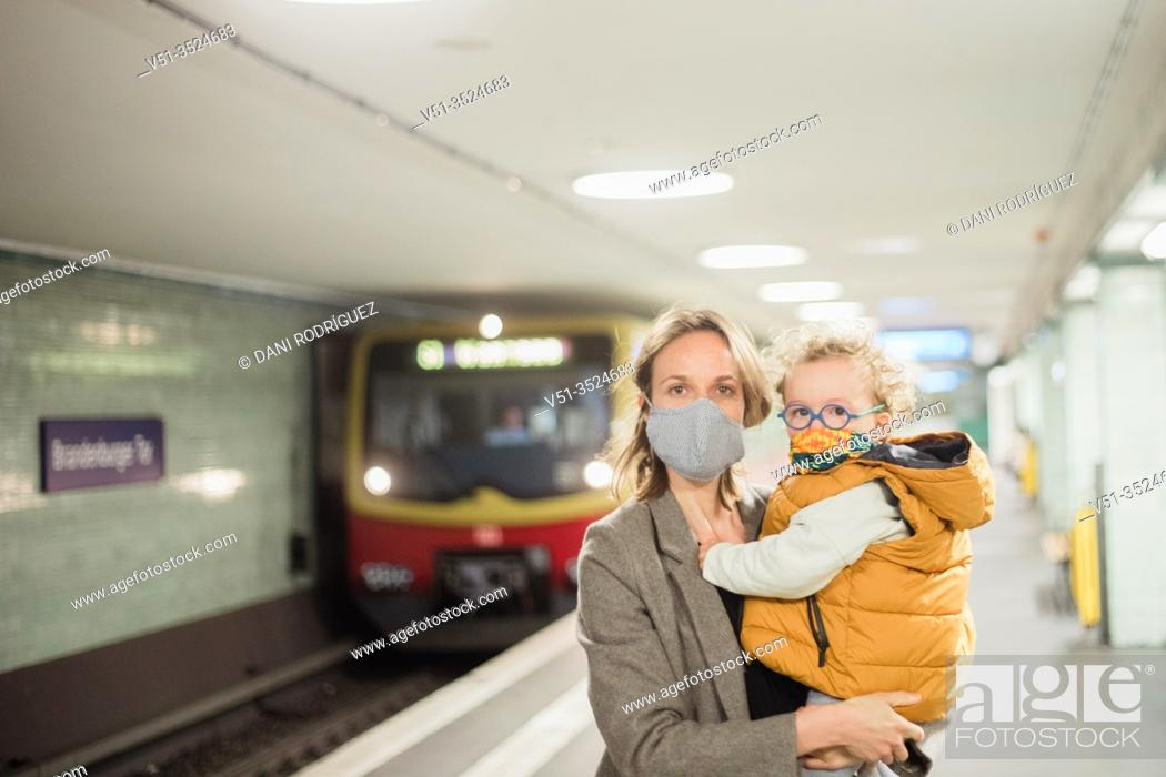 Imagen: Mother and son taking public transportation with mask during Corona days.