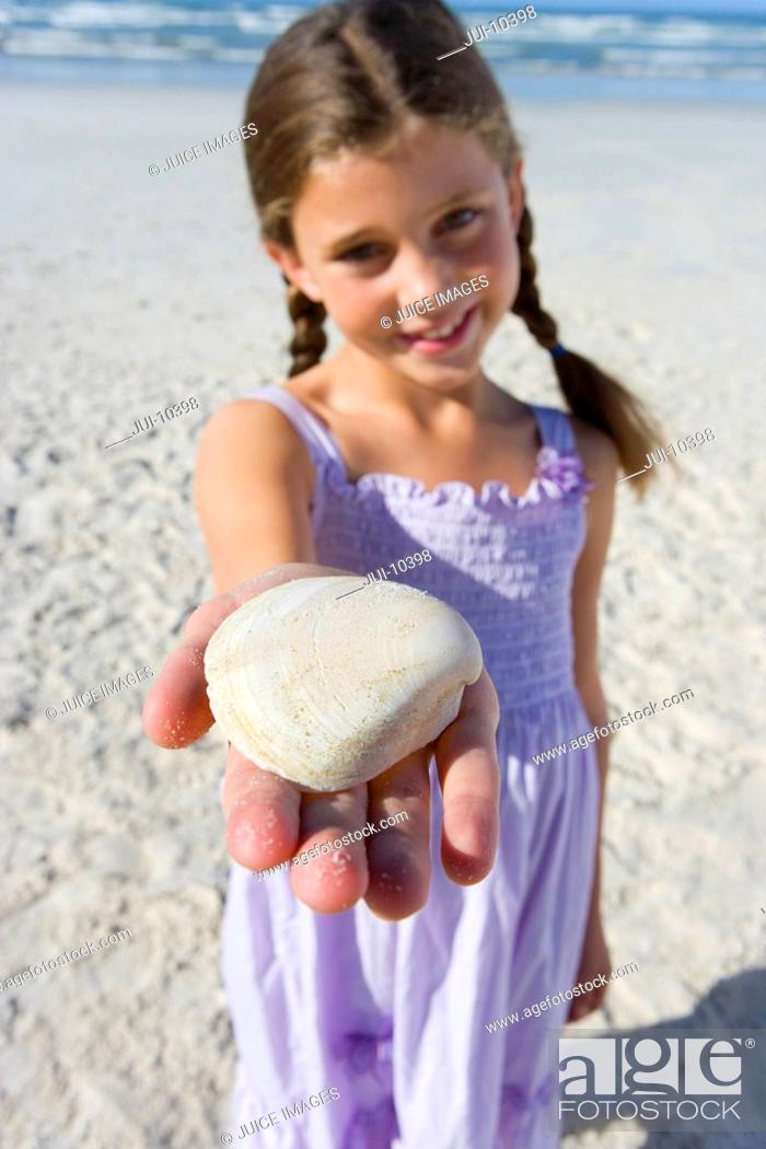 Stock Photo: Girl 5-7 with shell on beach, smiling, portrait differential focus.