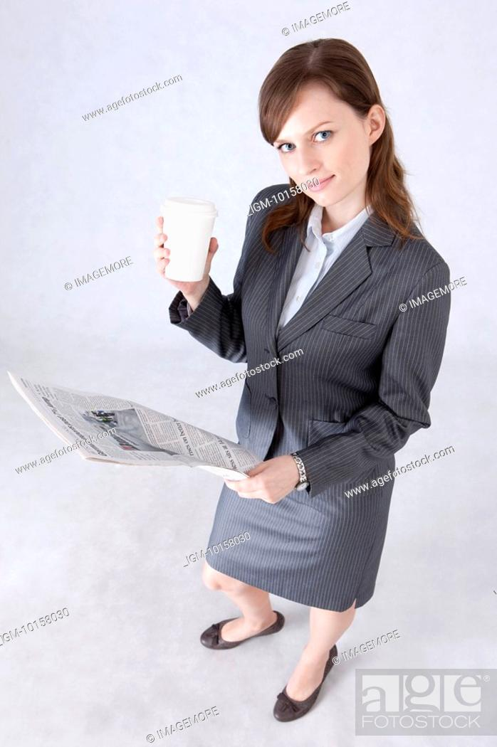 Stock Photo: Businesswoman holding a cup and newspaper and looking up.