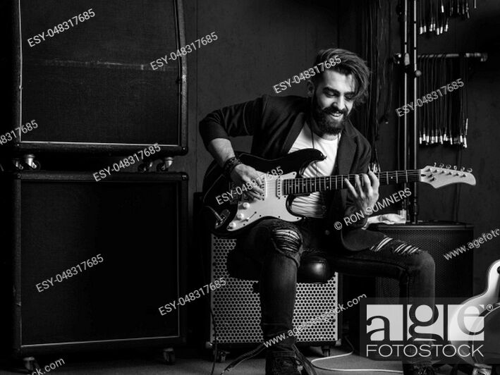 Stock Photo: Black and white photo of a man with beard sitting and playing his electric guitar in a recording studio.