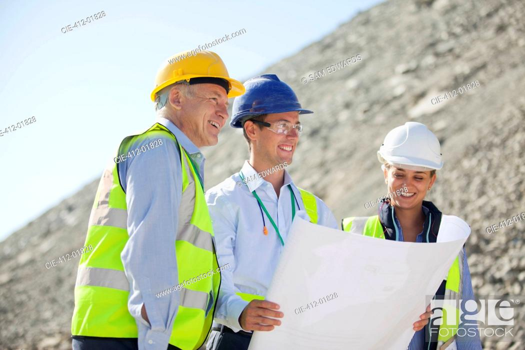 Stock Photo: Business people reading blueprints in quarry.