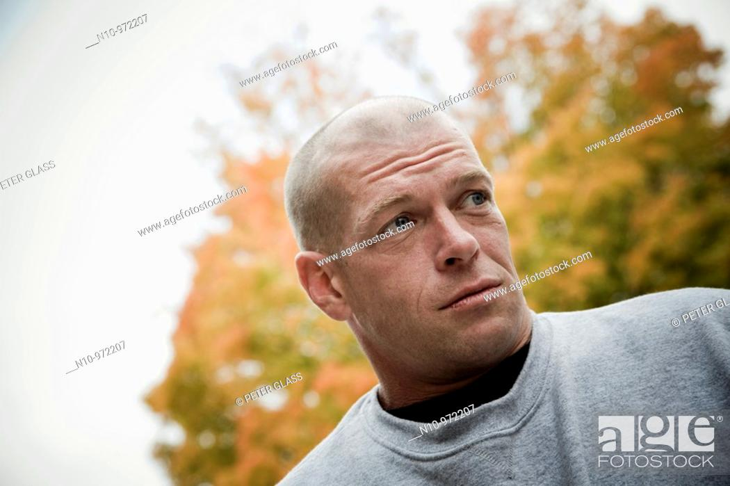 Stock Photo: Young bald man near trees changing color.