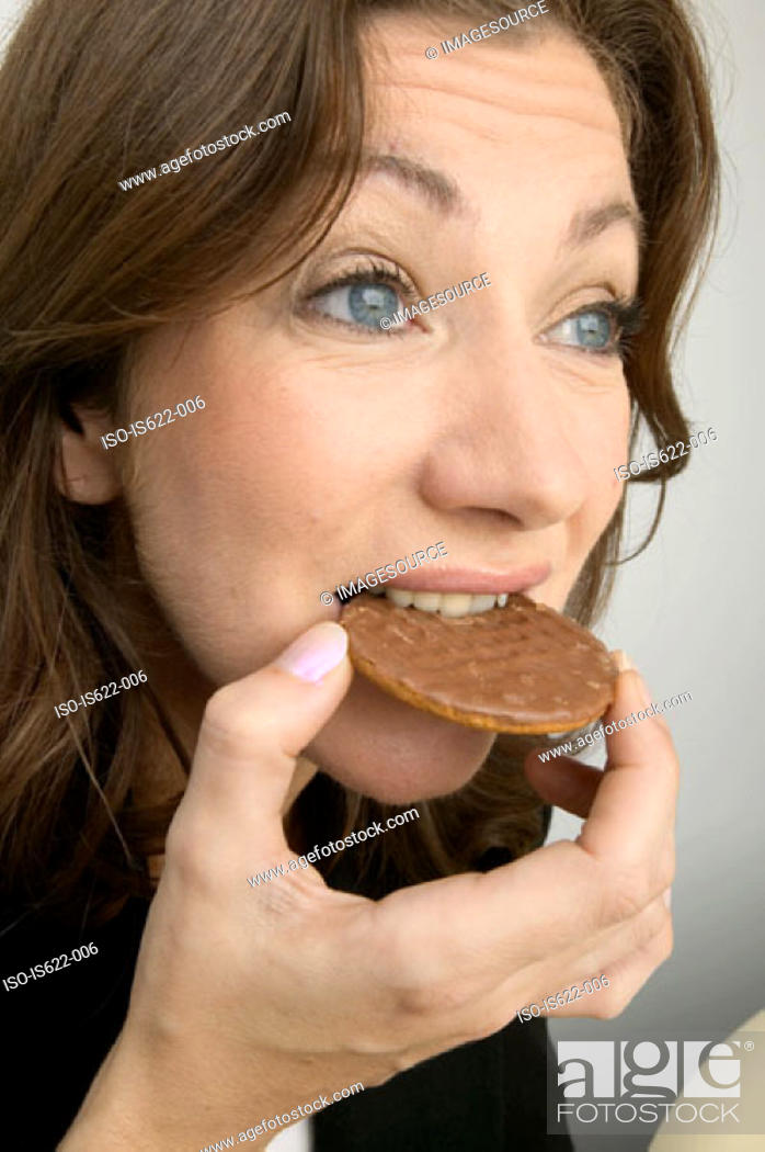 Stock Photo: Woman eating a chocolate biscuit.
