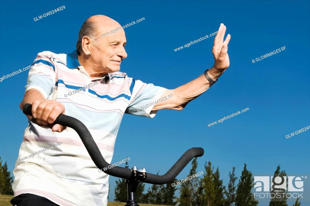 Stock Photo: Senior man on a bicycle and waving his hand.