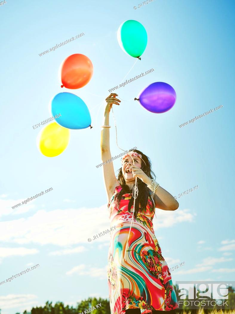 Stock Photo: Beautiful pregnant young woman feeling lovely and relax outdoors and she plays with a balloons.