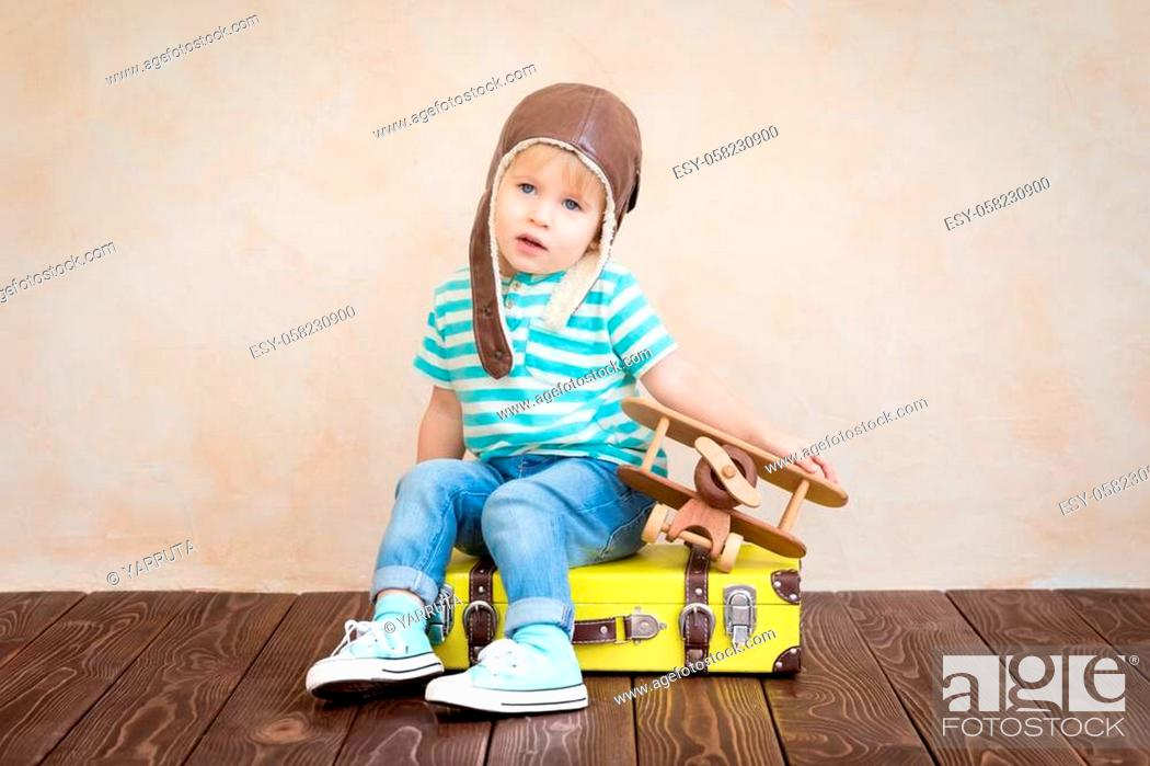 Stock Photo: Happy child playing with vintage wooden airplane. Kid having fun at home. Imagination and freedom concept.