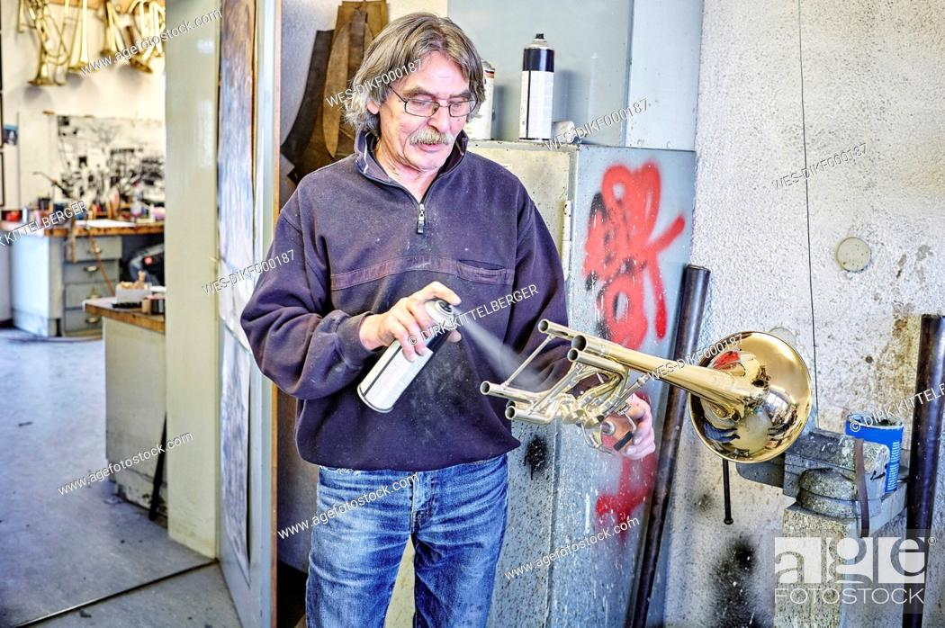 Imagen: Instrument maker using spray can for trumpet.