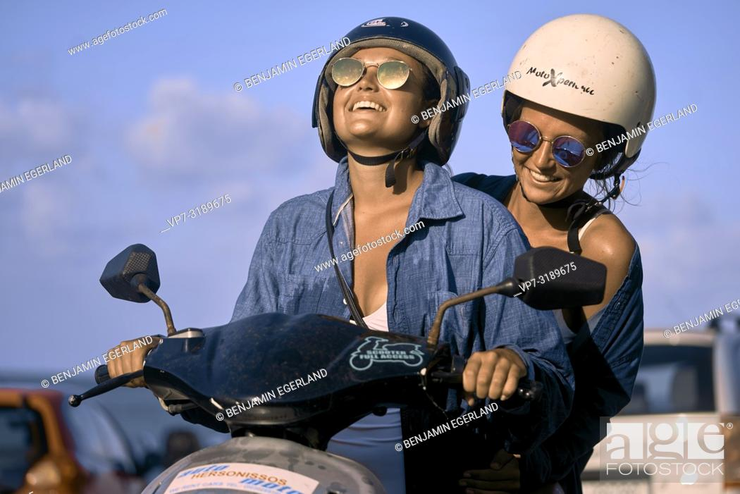 Stock Photo: Two women driving scooter, Chersonissos, Crete, Greece.