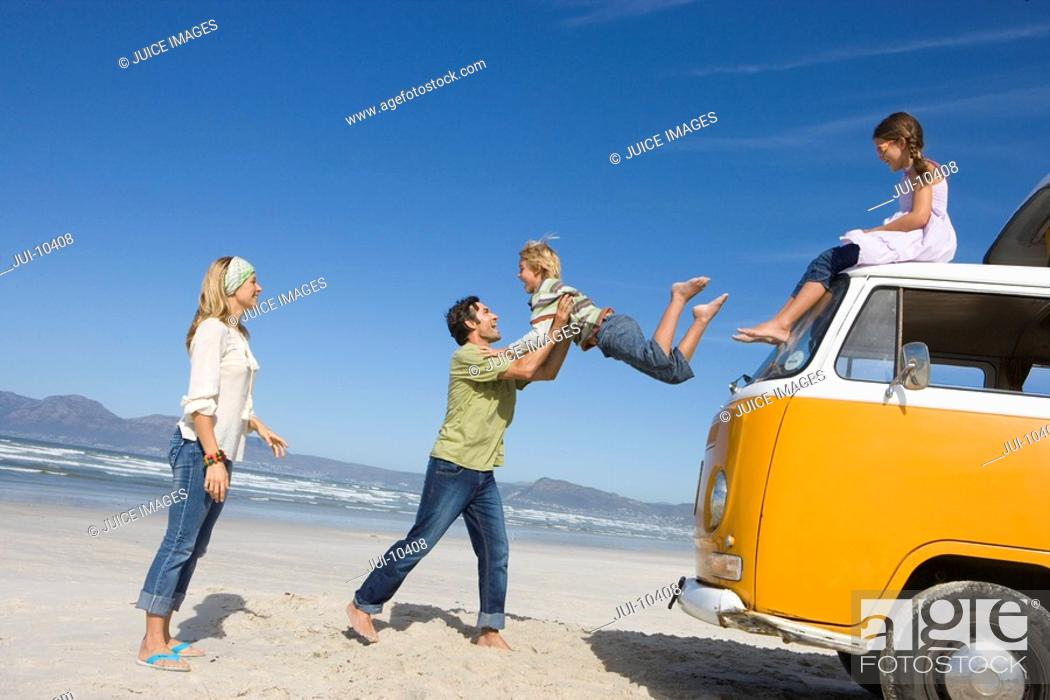 Stock Photo: Family of four on beach, father catching son 6-8 jump from roof of camper van, side view.