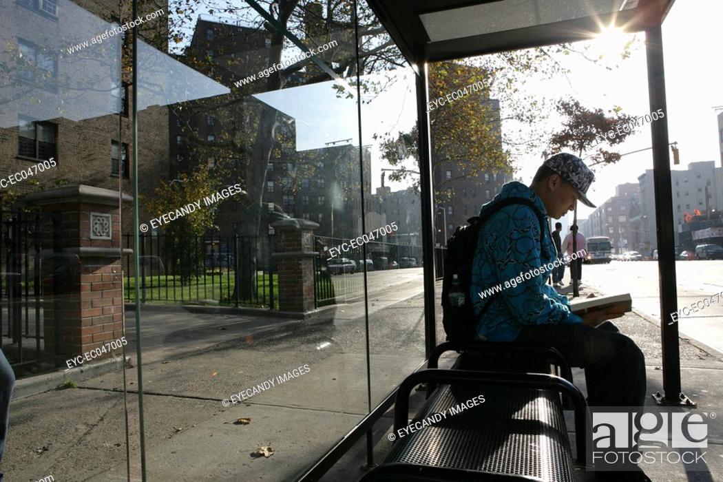 Stock Photo: Teenage boy 15-17 at bus stop reading book.