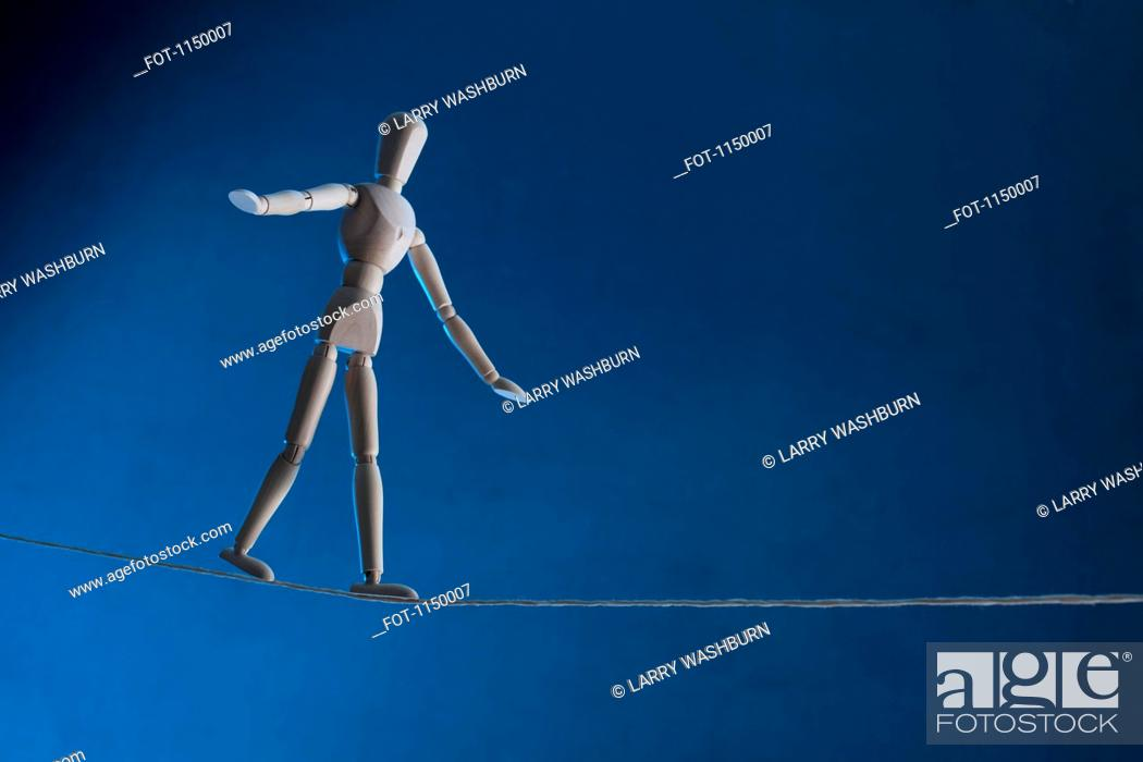 Stock Photo: An artist's figure walking a tightrope.