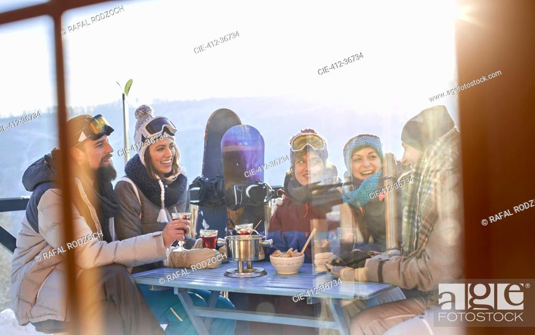 Photo de stock: Snowboarder friends drinking and eating at balcony table apres-ski.