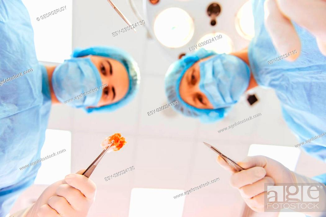 Stock Photo: Team surgeons are performing an operation using medical instruments, in a modern operating room, bottom view.