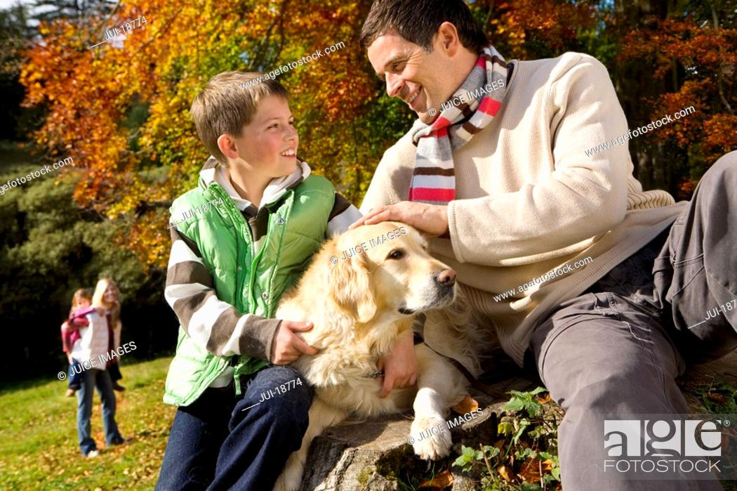 Stock Photo: Father, son, and dog sitting on tree stump in woods.