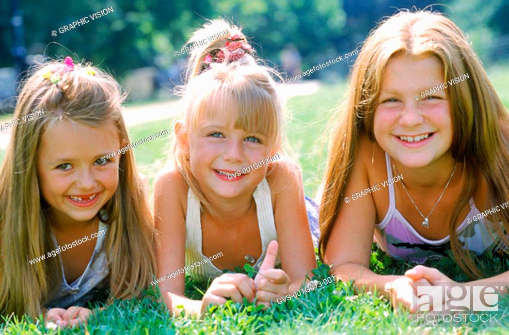 Stock Photo: Portrait of three girls lying on grass.