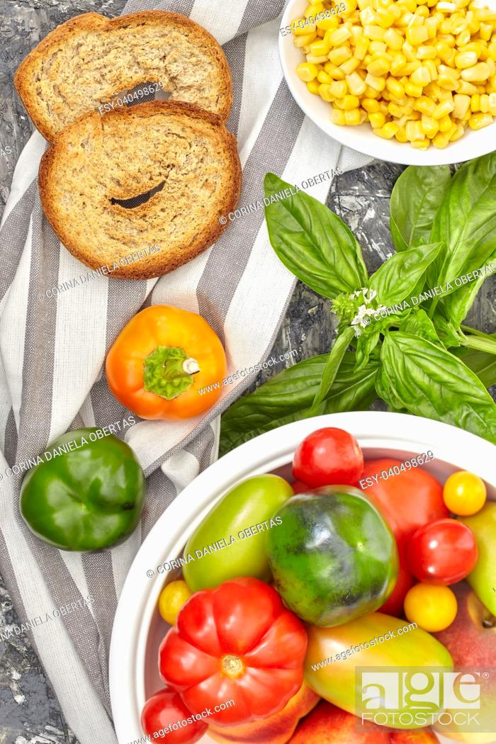 Stock Photo: Healthy ingredients mix with various types of tomatoes, bell peppers, corn, basil and apulian bread called frisella.