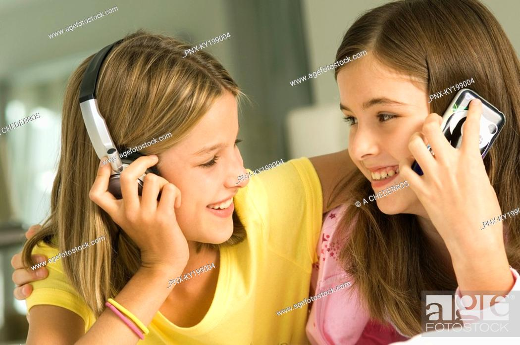 Stock Photo: Girl talking on a mobile phone and her sister listening to headphones.
